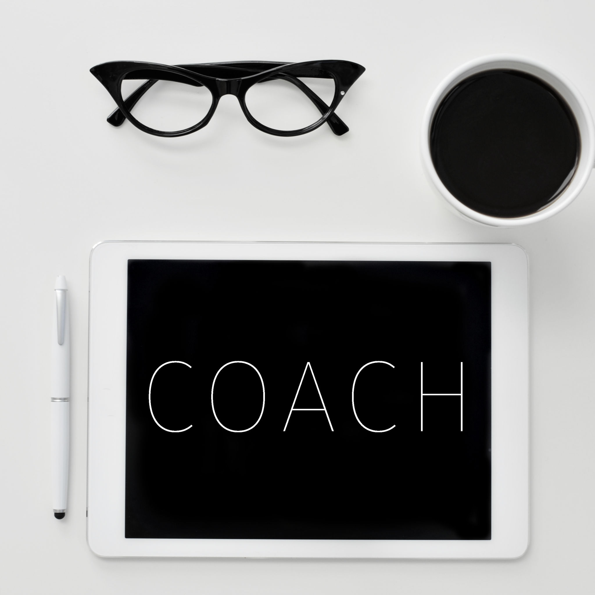 46738487 - high-angle shot of a desk with a tablet computer with the word coach written in it, a pair of women eyeglasses and a cup of coffee